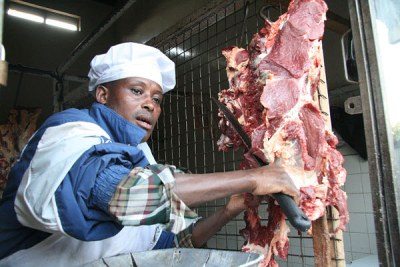 A butcher slices a piece of meat in butchery.