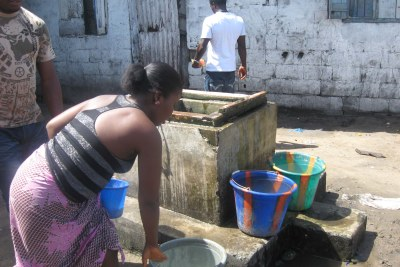 A woman fetches water from a well in a populated Monrovia slum.