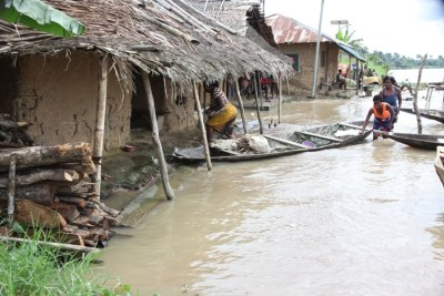 Women with a dug-out canoe in front of their flooded homes in Toru-Orua in Bayelsa state, Nigeria after the worst floods in 35 years.