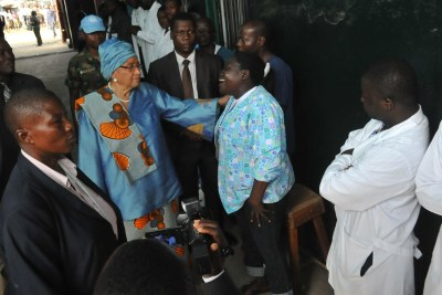 President Sirleaf consoles a health worker at the Redemption Hospital in Monrovia as they mourn the death of a colleague.