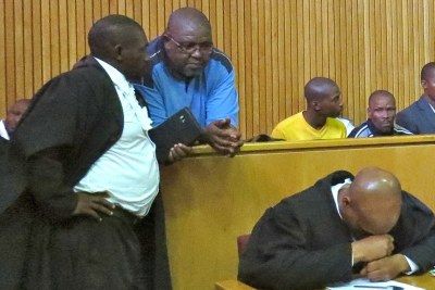 Jailed Swazi editor Bheki Makhubu in the dock, in blue, talking with his lawyer (file photo).