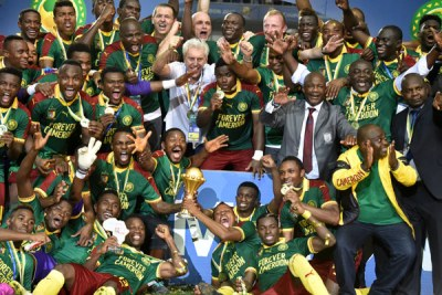 Cameroon team players and Cameroon's Belgian coach Hugo Broos (C) celebrate after beating Egypt 2-1 to win the 2017 Africa Cup of Nations final.