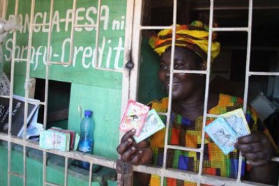 Bangla-Pesa grassroots coordinator Emma Onyango displays different notes of the currency at her shop in Bangladesh, Mombasa, on May 10, 2017.