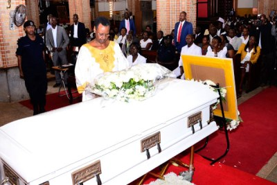 First Lady Janet Museveni lays a wreath on the casket containg the body of the proprietor and founder of St Lawrence Schools and Colleges, Lawrence Mukiibi during the requiem Mass at Rubaga Cathedral.