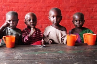 Quatre enfants congolais recevant de la nourriture à l'école grace au Programme alimentaire mondial (PAM). Ces tasses rouges sont le symbole de la campagne mondiale contre la faim à l'école.