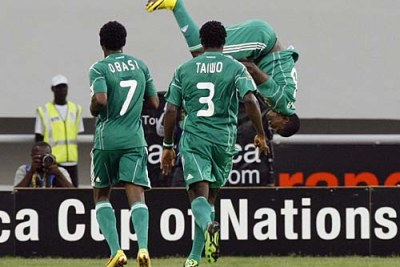 Obinna Nsofor of Nigeria, somersaults to celebrate a goal against Algeria with teammates Chinedu Obasi, 7, and Taye Taiwo, 3.