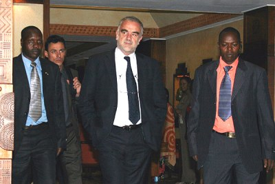 International Criminal Court Prosecutor Luis Moreno-Ocampo (centre) , with his security team, leaves the Serena Hotel for a meeting with a Cabinet sub committee on the investigations at Harambee House on May 10,2010.