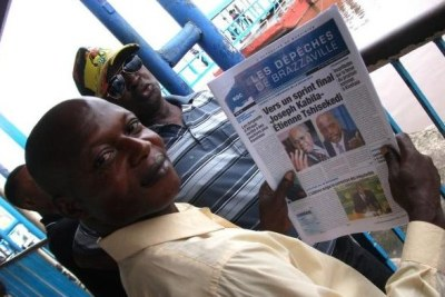 People on the ferry waiting to enter the DRC Man reading Brazzaville newspaper with headline,