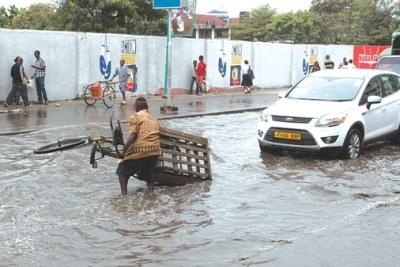A three-wheel bike rider saves his bike from stagnant water along Uhuru Road following floods that were caused by rains that battered Dar es Salaam (file photo).