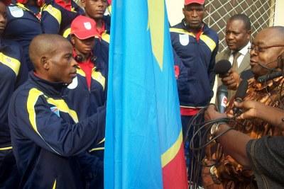 Le ministre des Sports, Baudoin Banza Mukalayi  remet le drapeau au porte-étendard de la délégation congolaise aux Jeux olympiques de Londres 2012