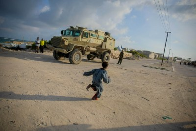 A young Somali girl runs in front of an African Union Mission in Somali (AMISOM) armed personnel carrier, Lido Beach in the Kaaraan District of Mogadishu, Somalia (file photo).