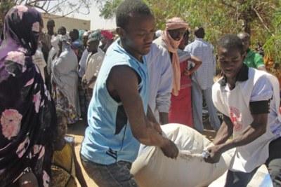 Gao (nord du Mali). Une famille de déplacés reçoit de la nourriture du CICR et de la Croix-Rouge malienne.