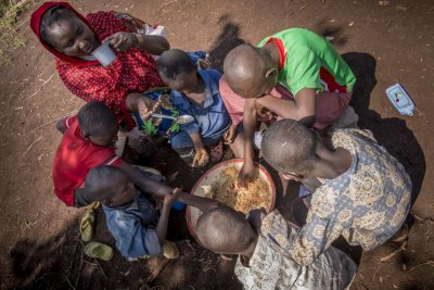 Six boys tuck into a bowl of food as Ramatou sips water from a cup in Mbile Refugee Camp, CAR.