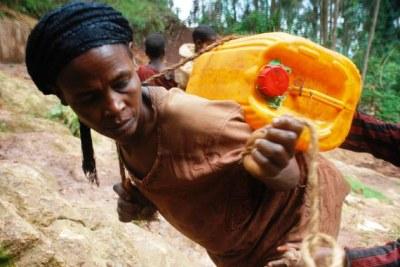 Femme portant de l'eau sur son dos.