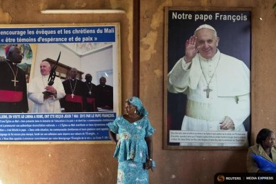 A woman stands in front of posters of Pope Francis at the Martyrs of Uganda church in Bamako, Mali.