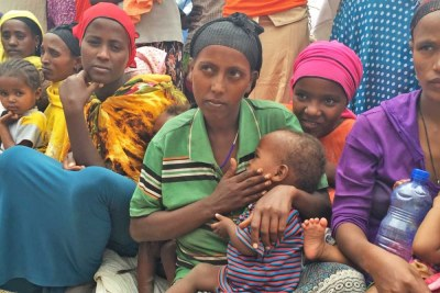 """Rahima Dadafe, a 23-year-old mother of four, is holding her youngest son, Nebiyu Jemal, age 1. She says the family is surviving on food assistance from the government, along with the special nutritious food from WFP to help baby Nebiyu recover from malnutrition. """"When the rain stopped raining, our crops failed and our livestock started dying because there was no grass for them to feed on. I had three cows. They all died. Now we are {living on} the assistance from the government."""" she said."""