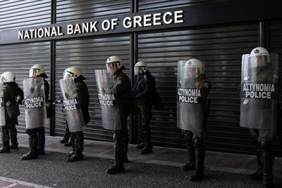 National Bank of Greece Guarded. Workers take to the streets against cutbacks.Tens of thousands of striking Greek workers took to the streets, some throwing stones at police, in a defiant show of protest against austerity measures aimed at averting the debt-plagued country's economic collapse.