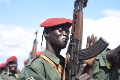 A South Sudanese government army soldier slaps his gun at Jebel Makor, 45 minutes outside South Sudan's capital Juba,