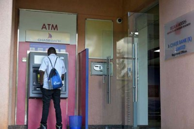 A customer at an ATM at the Chase Bank head office branch in Nairobi.