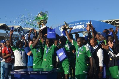 Gor Mahia players and officials celebrate with SportPesa Super Cup trophy and medals after defeating their Kenyan traditional rivals AFC Leopards in a thrilling match final held at the Uhuru Stadium in Dar es Salaam.