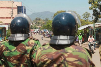 Police officers look on during anti-IEBC protests (file photo).