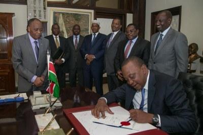 President Kenyatta signs a bill into law (file photo).
