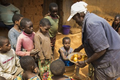 70 years old William Ajili shares his familly's food with refugees fro Cameroon.