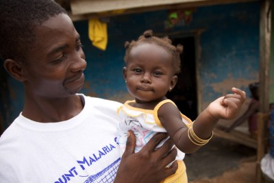 A Ghanaian volunteer who distributed malaria nets, with his daughter.