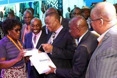 VP Chiwenga receives a present during his tour of the Econet Wireless stand at the ZITF.