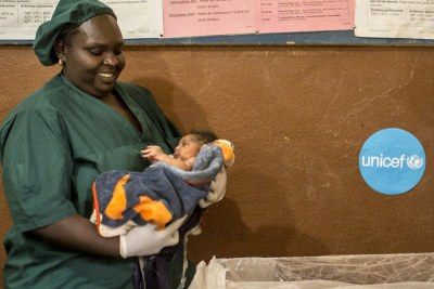 Midwife Fadimata Maïga holds a newborn infant before placing it beneath an infant radiant warmer in order to proceed to a newborn health assessment at the Baraouéli Health Center in Baraouéli, Ségou region, Mali.