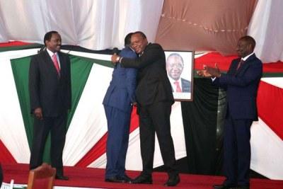 President Uhuru Kenyatta hugs Opposition leader Raila Odinga as his Deputy President William Ruto (right) and Wiper leader Kalonzo Musyoka cheer them at the National Prayer Breakfast meeting (file photo).