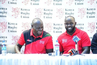 Kenya Sevens coach Innocent Simiyu (left) and his Lionesses counterpart Kevin Wambua enjoy a light moment after naming their teams for Hong Kong, Singapore and Commonwealth Games on March 28.