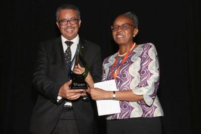 * Dr. Matshidiso Moeti, Directrice régional de l'OMS pour la Région africaine, recevant le Prix du partenariat innovant pour la couverture universelle en matière de santé du Dr. Tedros Ghebreyesus, Directeur général de l'OMS. *
