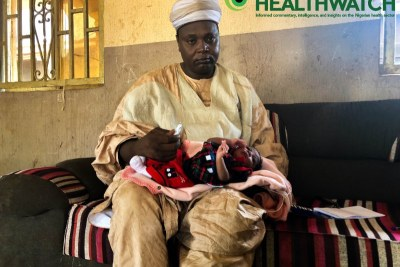 Sarkin Gagi, Alhaji Umar Jabbi with his newborn baby. In his hand is a Chlorhexidine gel which is being applied on the boy's unbiblical cord area.