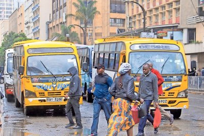 Commuters walk past matatus on the road within the city centre on December 4, 2018.