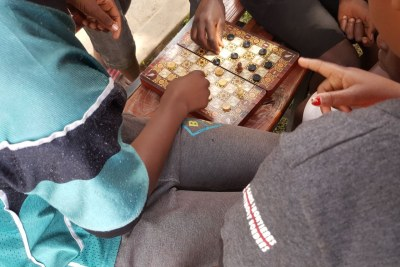 Peer leaders playing board games with young boys at the adolescent centre.