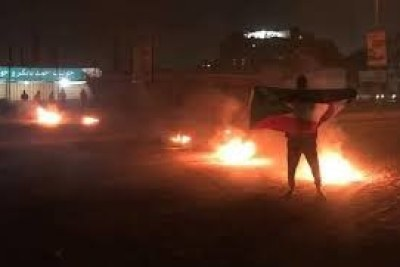 A protester holds a Sudanese flag at a street blockade in Omdurman (file photo).