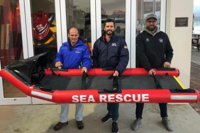 The Purpose Designed Rescue Stretcher with (picture centre): NSRI Plettenberg station commander, Marc Rodgers. (and picture left): the manufacturer of the rescue stretcher, Marcus van Deventer. (and picture right): NSRI Plettenberg Bay coxswain, Robbie Gibson.