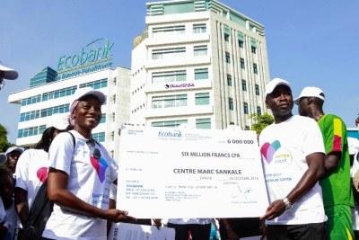 La Directrice du centre diabétologie Marc Sankare recevoir le chèque d'Ecobank pour la structure qu'elle dirige