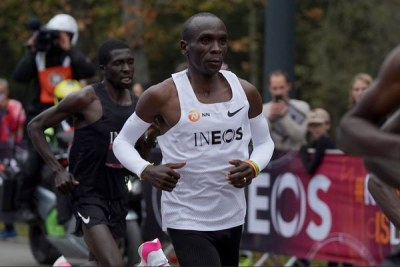 Eliud Kipchoge (in white) runs flanked by pacesetters during the INEOS 1:59 Challenge at Prater Park in Vienna, Austria on October 12, 2019.