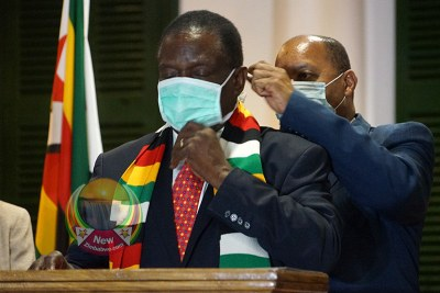 Health Minister Obadiah Moyo adjusts President Emmerson Mnangagwa's face mask at State House.