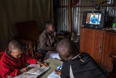 12-year-old Elizabeth and 10-year-old Justin follow a Social Studies lesson on the EDU TV while doing their revision at home in Kibera. Justin's brother, Morara who is in the kindergarten doodles on an exercise book. Elizabeth is in Standard 6 and Justin is in Standard 5,