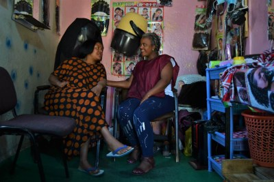 Former migrant worker Yenenesh Tilahun and her associate Saba Belete pose in their beauty salon in Addis Ababa, Ethiopia, February 24, 2021.