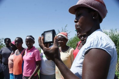 A member of the Kamolo beach group in western Kenya displays the solar light helping women around Lake Victoria to go fishing, January 17, 2021.