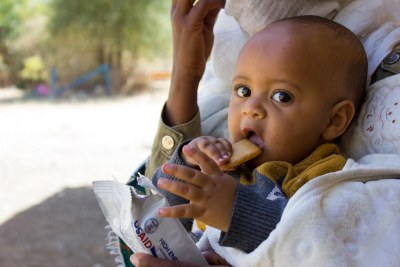A small child eats a nutritious high-energy biscuit at a school that has been converted into a shelter in the Tigray region where the UN humanitarian agency OCHA estimates that 91 per cent of the population is in dire need of food assistance.